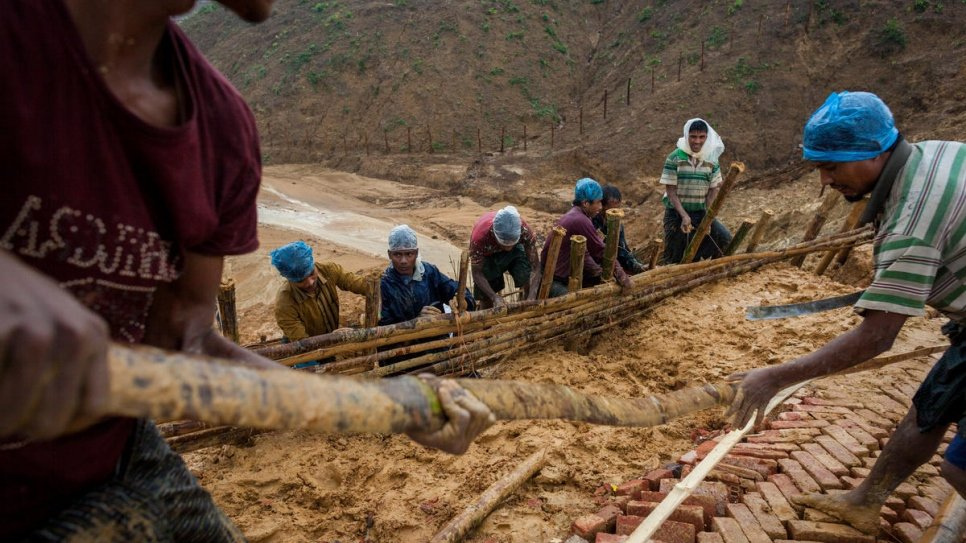 Supervised by UNHCR, Rohingya workers build an all-weather footpath as heavy rains threaten Kutupalong refugee settlement, Bangladesh.