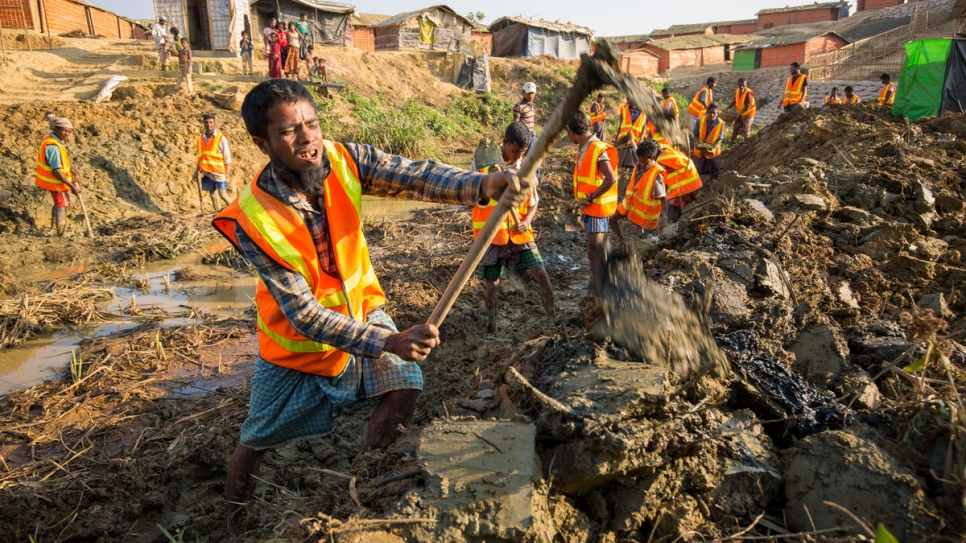Rohingya refugees clear a drainage channel at Kutupalong settlement in Bangladesh, as part of a joint UNHCR, IOM and WFP project to mitigate monsoon flooding.