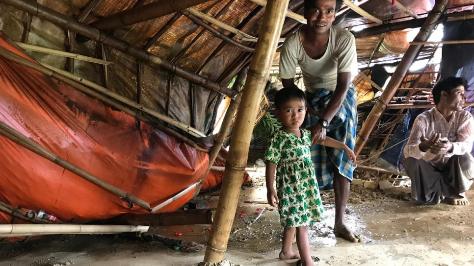 Mohammed Rafiq and his two-year-old daughter, Noor Fatima, inspect their shelter damaged by a landslide at Chakmarkul settlement, Bangladesh.