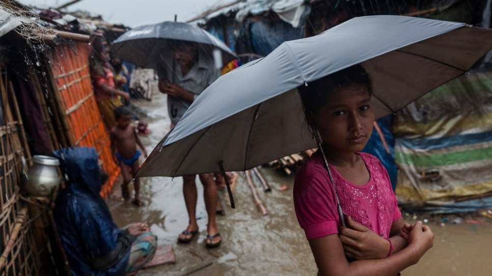 A young Rohingya girl stands in the rain at a refugee settlement in Shamlapur, southeast Bangladesh.