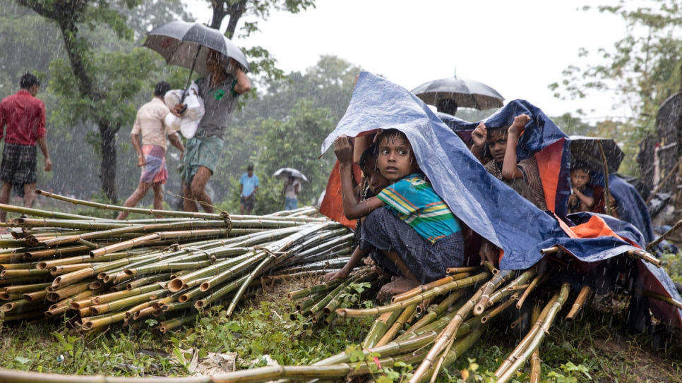 Rohingya children shelter under tarpaulin as heavy rain falls at Kutupalong.