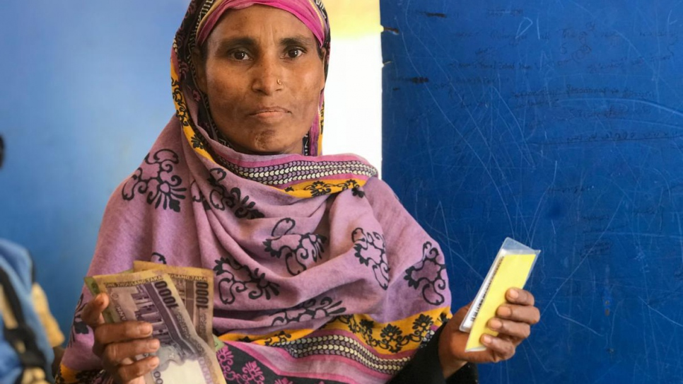 "Rohingya refugee and single parent Samuda, 35, receives UNHCR cash assistance in Bangladesh, April 2018. She says: ""The first thing I'll do is pay off our debts and then we'll use this money to buy food."""