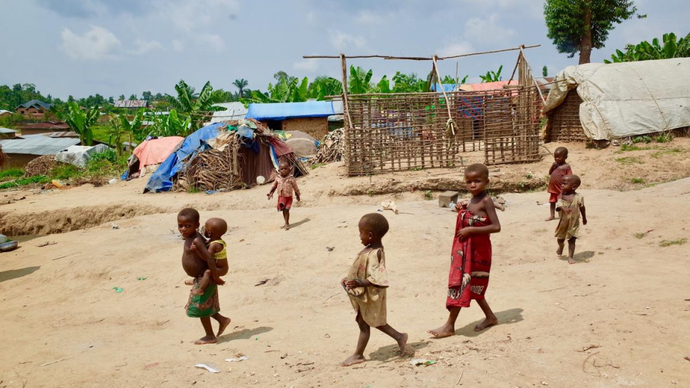 Children walk through a makeshift site hosting internally displaced members of the Mbuti indigenous community in Oicha's Ruvangira neighbourhood, in North Kivu province.