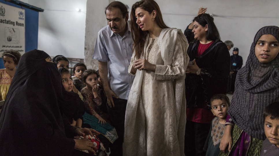 Pakistani actor Mahira Khan speaks with Afghan refugees at a UNHCR voluntary repatriation centre in Peshawar, Pakistan. The refugees are preparing to return home to Afghanistan.