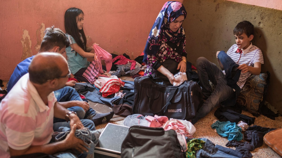 Zain, right, sits by his mother Nour as his family pack for their move to Norway.