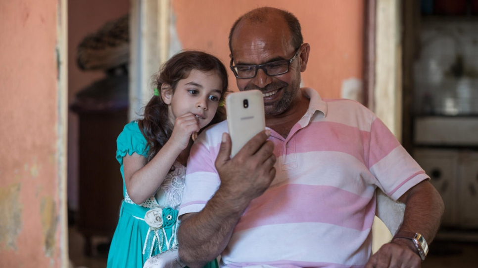 Zain's father Ali and sister Riman smile as they talk to a cousin already living in the Norwegian town of Hammerfest.