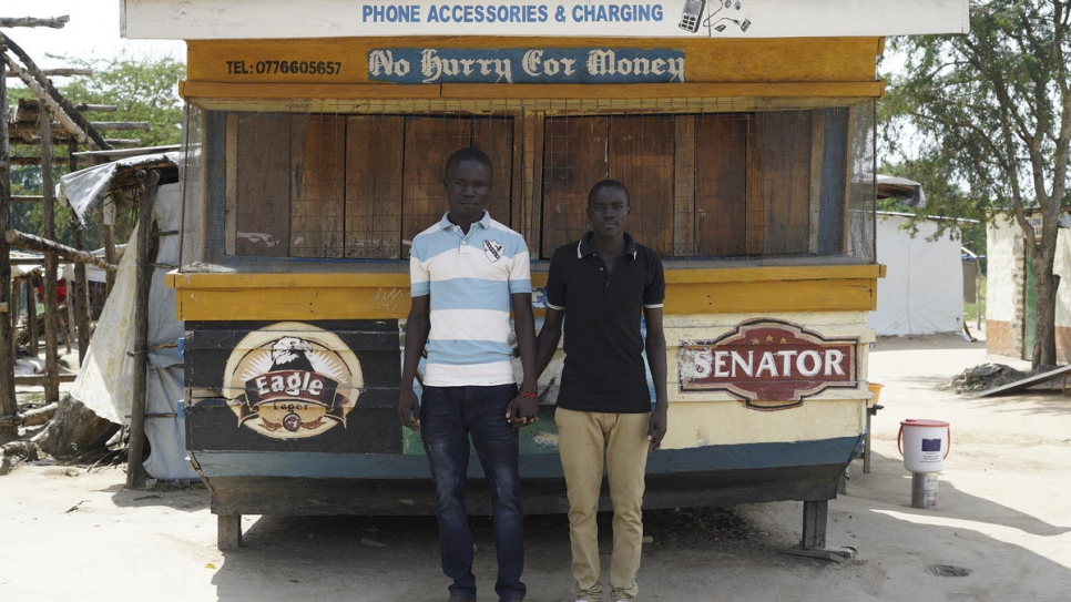 South Sudanese refugees stand in front of the phone shop they are opening soon.