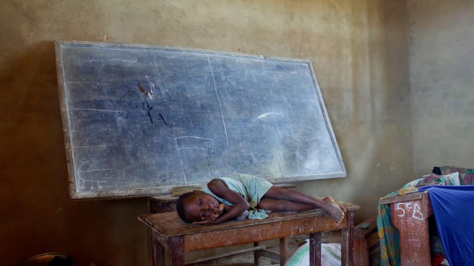 Agnes' daughter, Rebecca, lays on a table in the classroom of the school where they are living in Oicha, Beni territory, in North Kivu province.