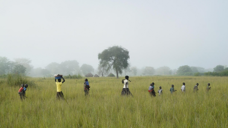 Queen's children help out on her land at Oligi settlement, where she grows rice.