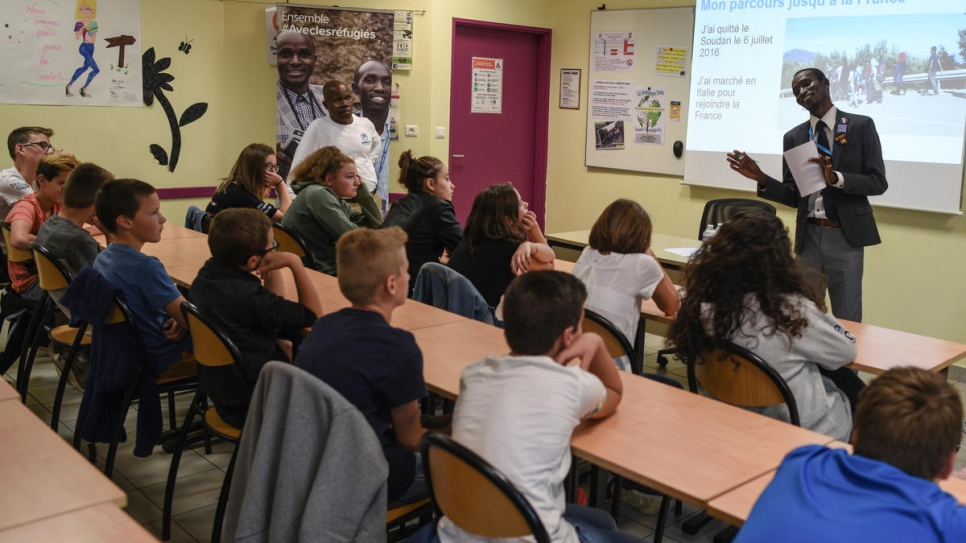 Pupils listen to Sudanese refugee Hassan Mahamat tell the story of his journey to France via Libya and the Mediterranean.