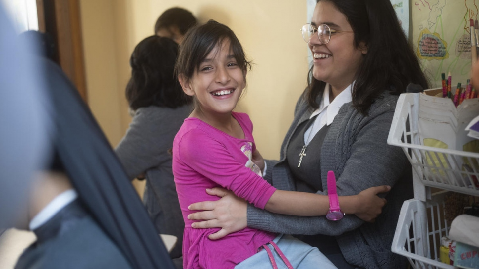 A Venezuelan child interacts with a volunteer at the Hearts Without Borders childcare centre in Bogotá, Colombia.