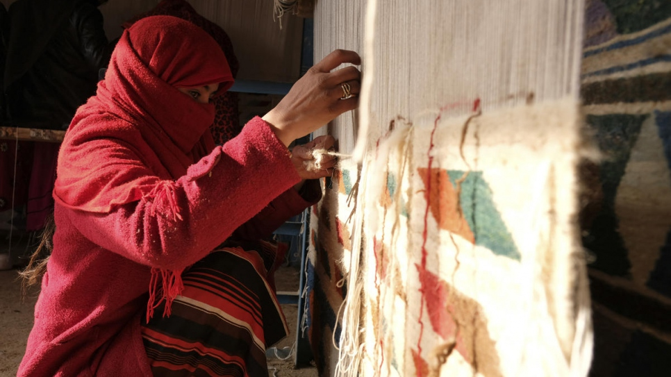 A weaver makes a carpet in Afghanistan's northern Balkh Province in December 2017. The woman and her family are displaced from Faryab province and came to Balkh in 2017.