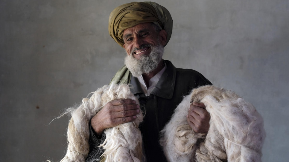 An Afghan returnee holds wool he sorts out for women spinners. The thread goes to make carpets and kilims as part of UNHCR's community based livelihoods project in Kabul, December 2017.