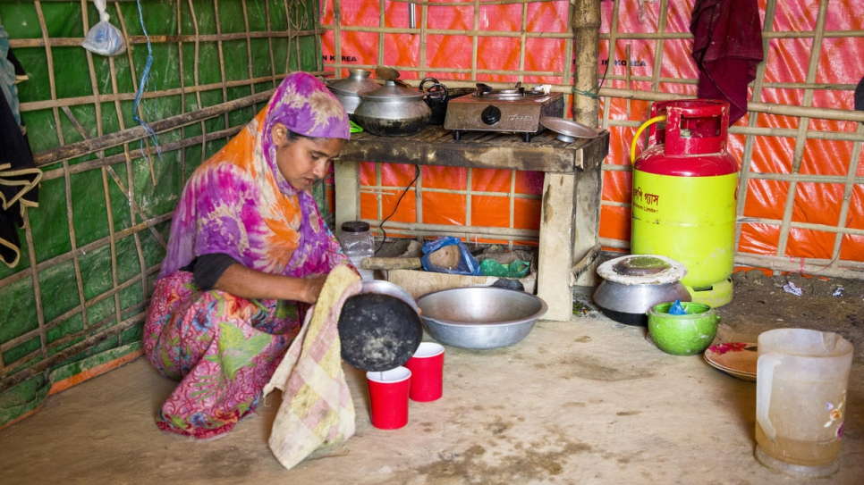 Monowara uses her gas stove to cook for her family. UNHCR has launched a programme to 