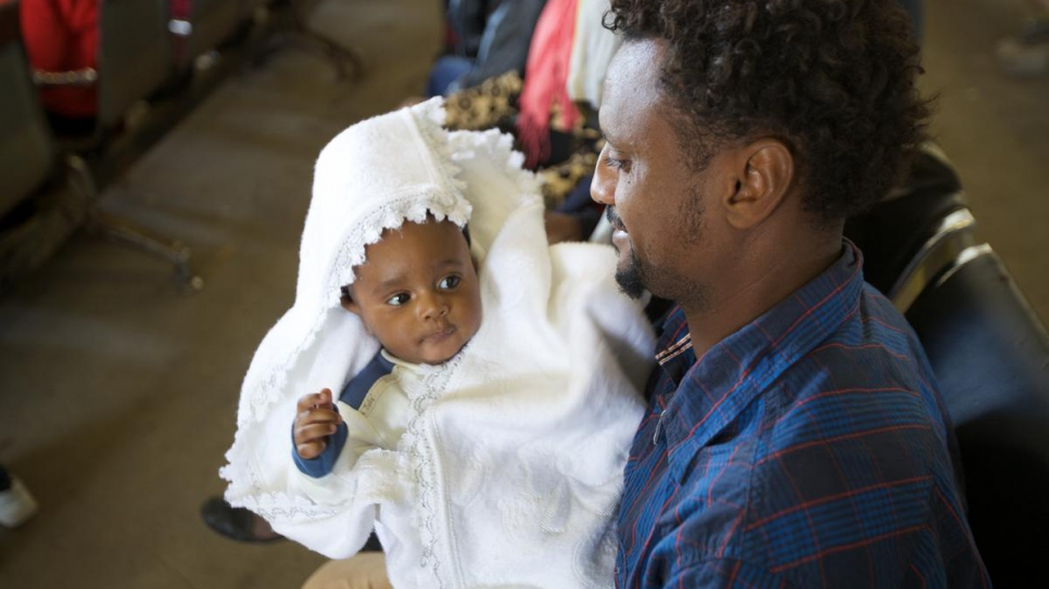 An Eritrean man proudly cradles his daughter while waiting to be evacuated to Niger.