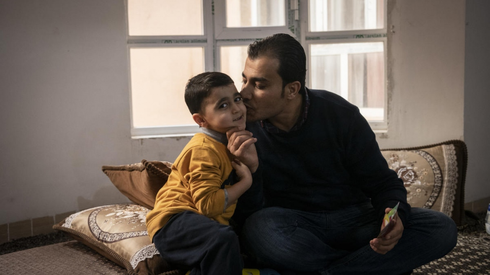 Mohammed Issa helps his five-year-old son Issa with his English homework in their home in Erbil, the capital of the Kurdistan Region of Iraq.