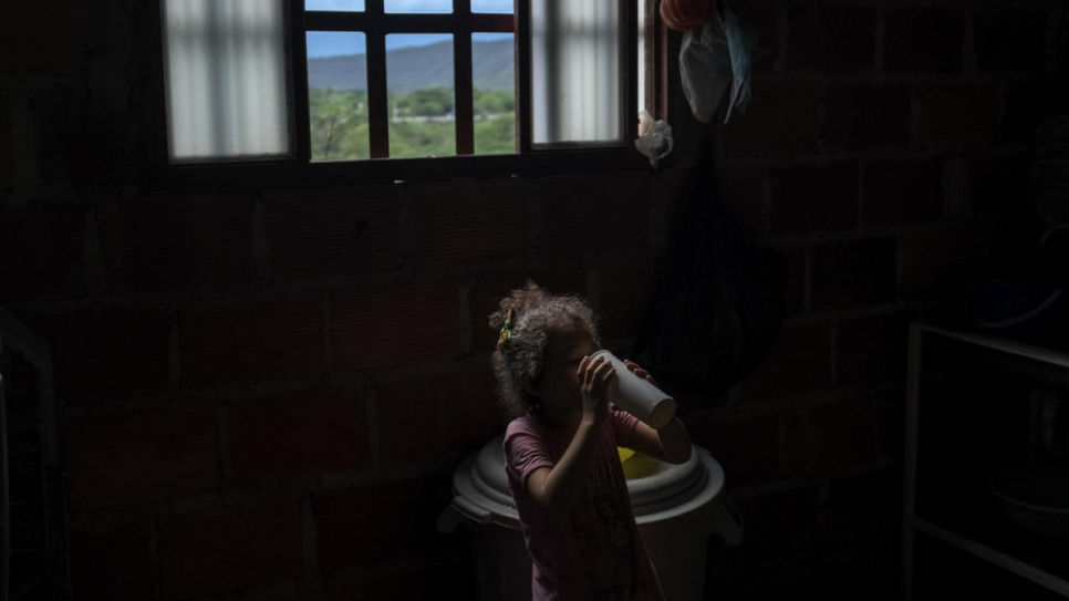Little Yaniz, from Venezuela, drinks a glass of water inside Graciela Sanchez's home in Las Delicias community in Cúcuta.