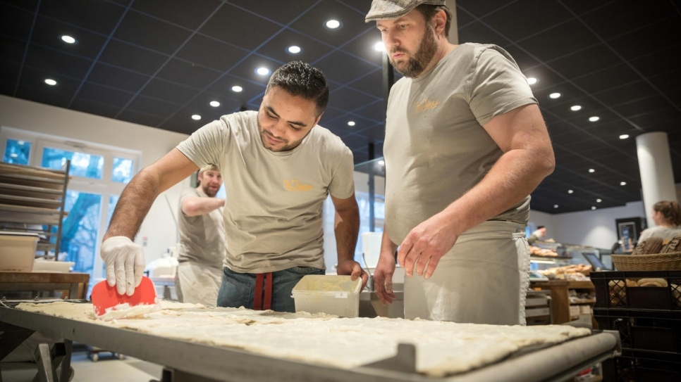 Master baker Björn Wiese (right) teaches Mohamad how to prepare the dough.