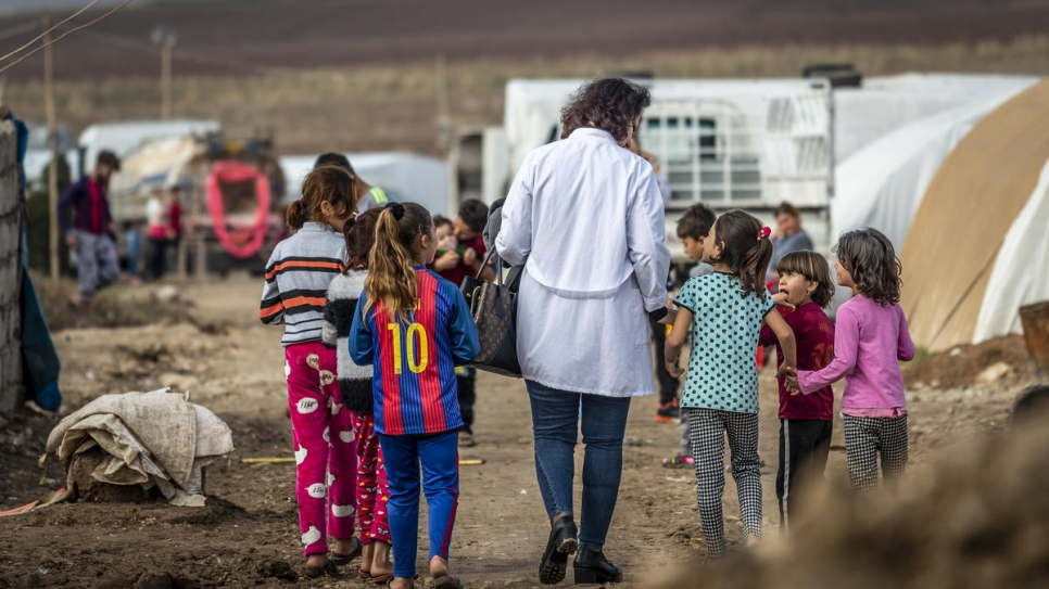 Nagham Nawzat Hasan visits an informal tented settlement for displaced people in Duhok Governorate in the Kurdistan region of northern Iraq..