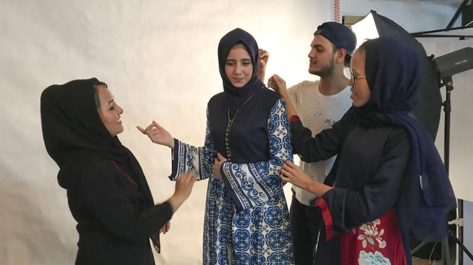 Franka Soeria (in navy blue headscarf) helps some of her refugee fashion students with last-minute adjustments before a photoshoot at her Markamarie workshop in South Jakarta.