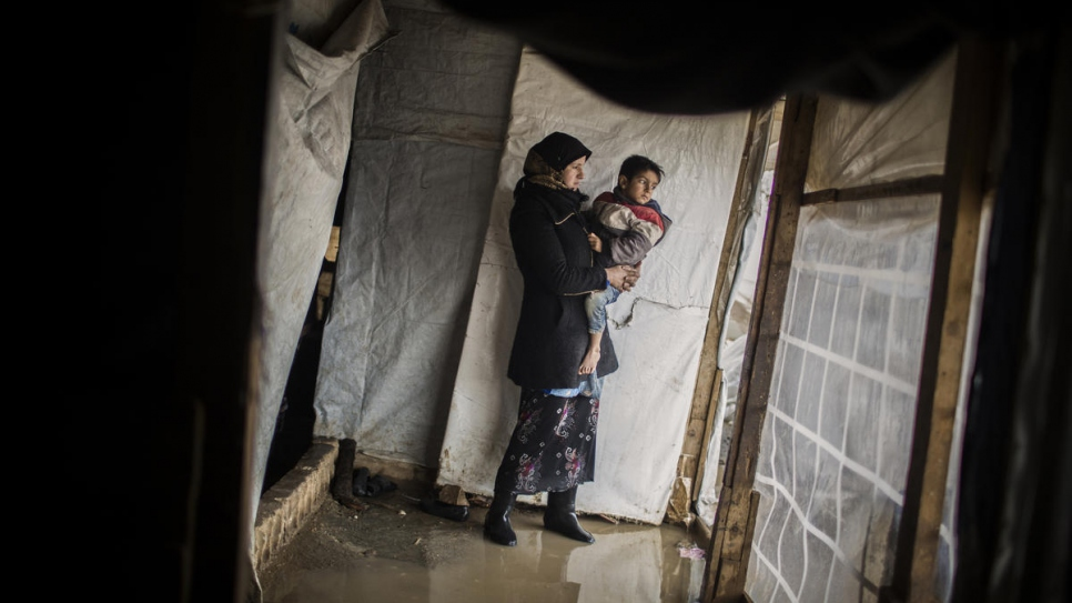 Juriya Ramadan holds one of her children as she inspects her flooded house at Dalhamiya informal settlement camp in Bekaa Valley, Lebanon.