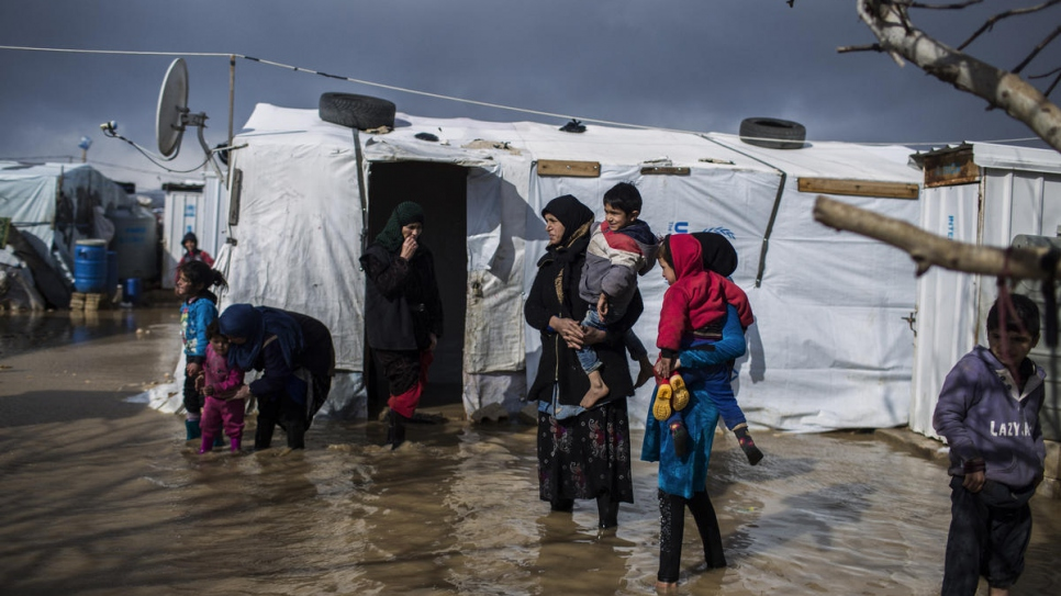 Juriya Ramadan, who fled from Deir El Zor in Syria, walks the flooded streets of  Dalhamiya informal settlement camp in Bekaa Valley, Lebanon.