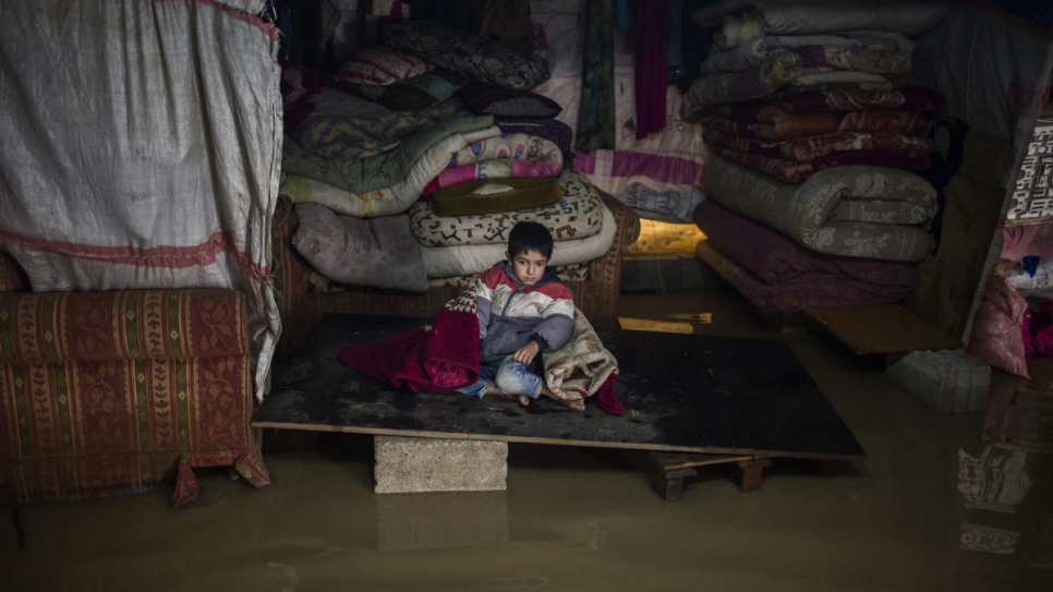 One of Juriya Ramadan's sons sits inside his flooded tent. The tent collapsed as a consequence of Storm Norma's violence.
