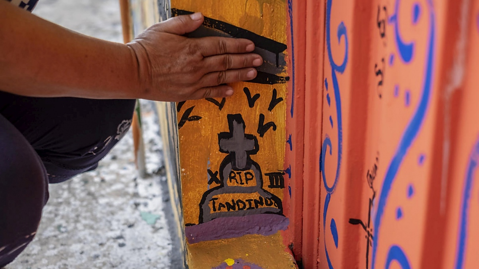 Janeth shows the tomb she painted in the mural to express her grief. Her 17-year-old son was killed by a criminal gang in El Salvador in 2017 because he refused to join.