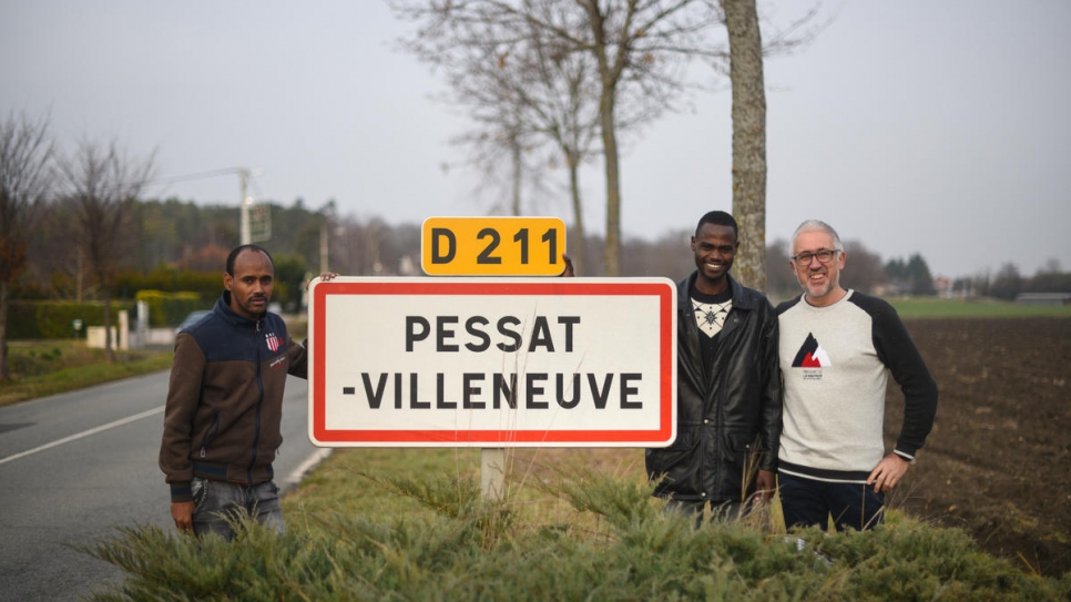Mayor of Pessat-Villeneuve Gerard Dubois, with resettled refugees Ibrahim and Alfatih.