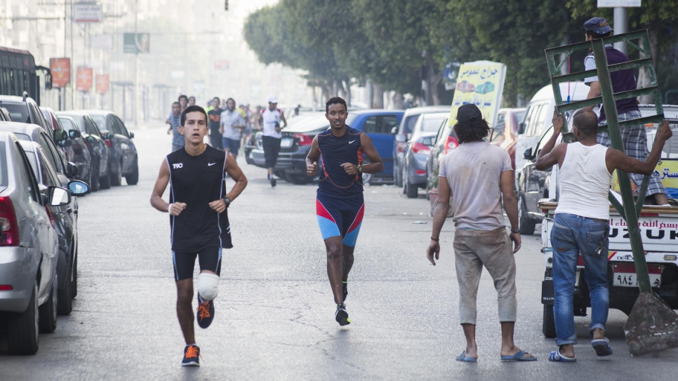 """Whenever I am running I feel free, living in a free world of my own."" Guled (centre, in blue and orange running top) participates in the Cairo Runners Club run in the Heliopolis suburb of the Egyptian capital."