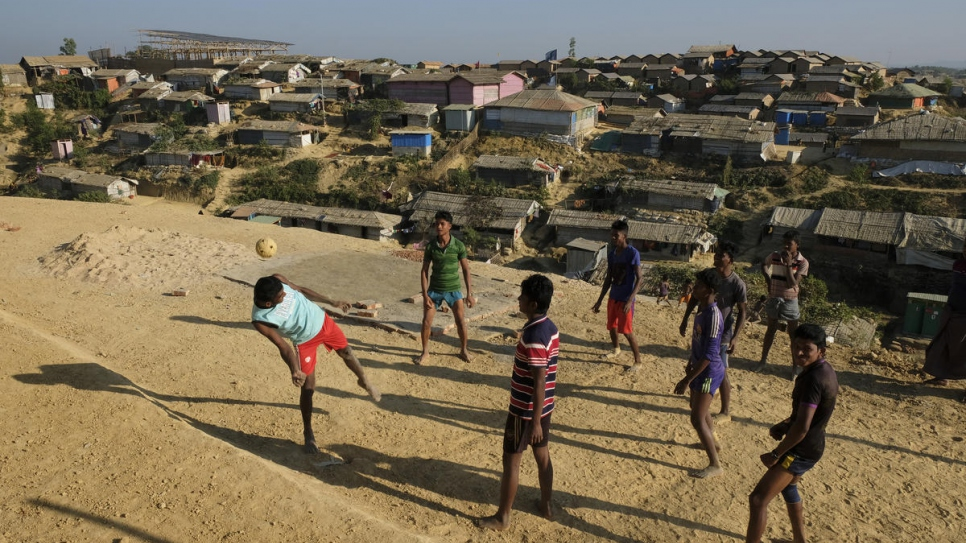 Rohingya youth play a game of football in a clearing at Chakmarkul refugee camp in Cox's Bazar, Bangladesh.