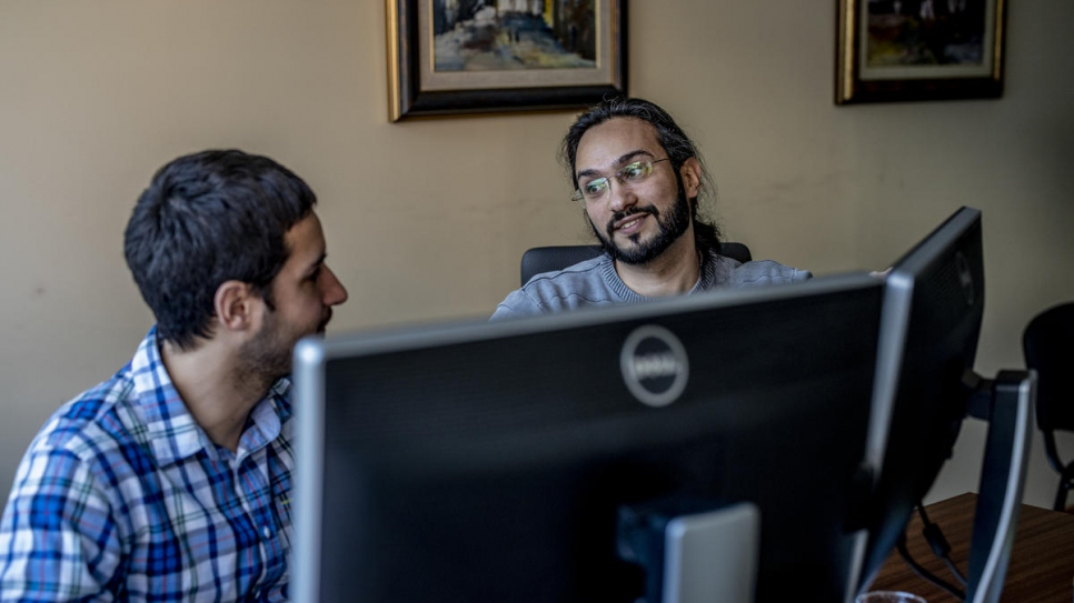 Mawaheb speaks with a colleague at his office. He works as a software engineer for an energy company in Belgrade.
