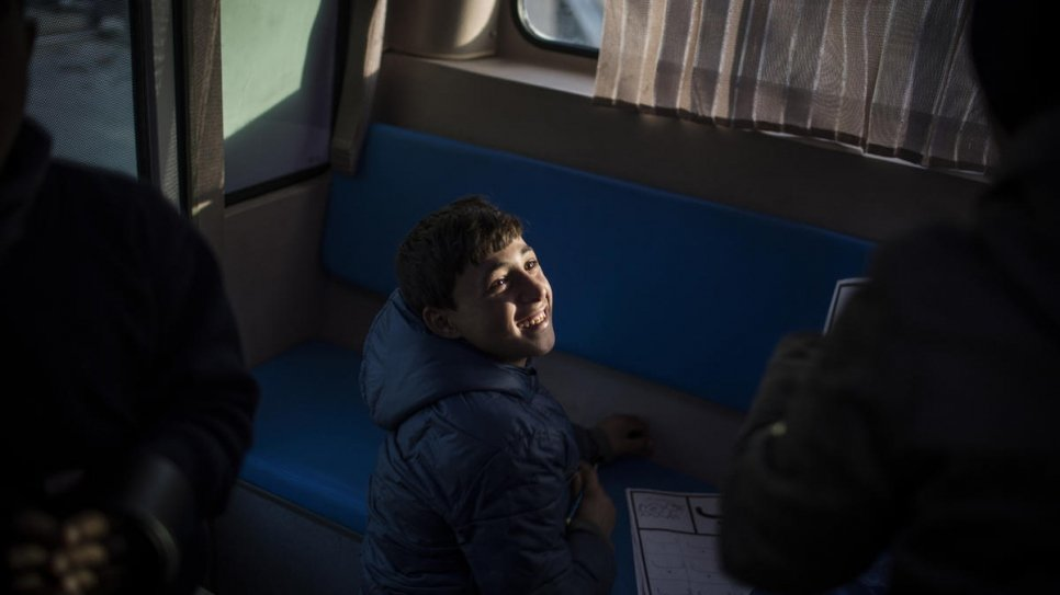 "Alaa, a Syrian refugee from Aleppo who sells water at a busy intersection, learns the alphabet inside the ""Fun Bus""."