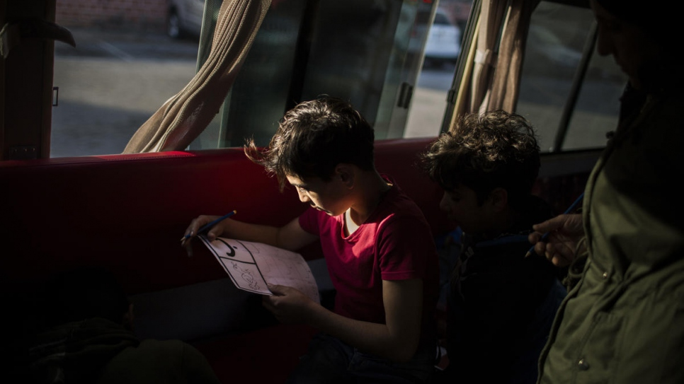 A child learns to read during his weekly visit onboard the bus.