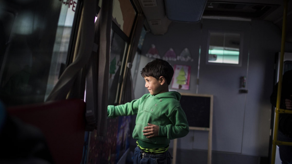"Ezzo, a 6-year-old Syrian refugee from Aleppo, looks through the window of the ""Fun Bus""."