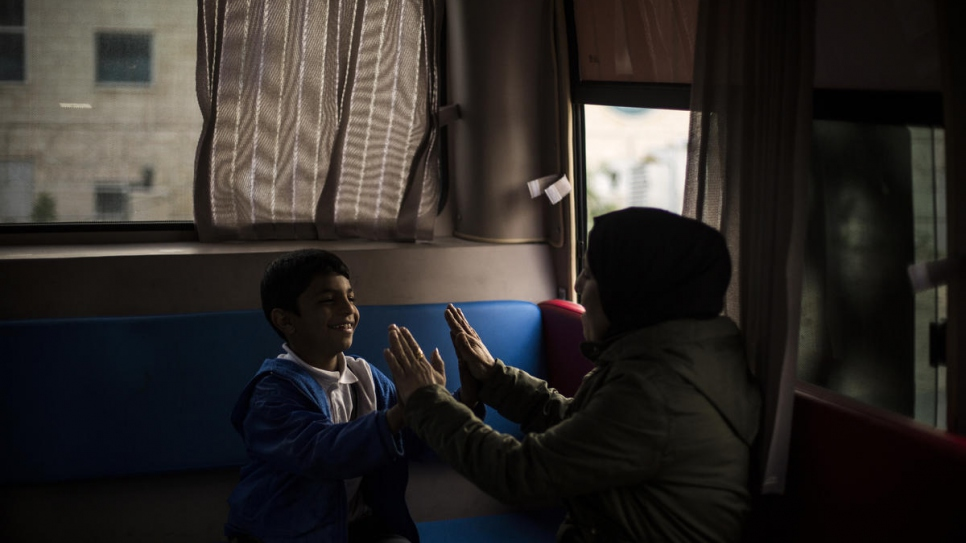 A young Syrian refugee plays with one of the outreach volunteers who works on the bus.