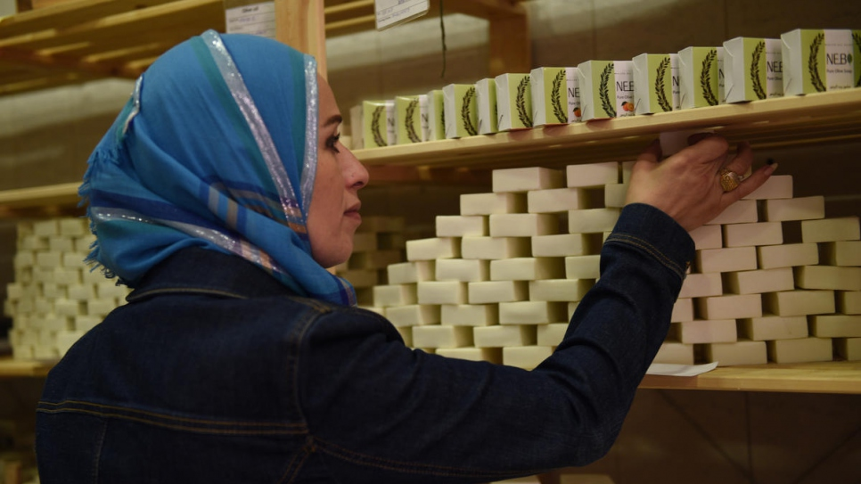 Susan stocks the shelves with soap at their premises in Zarqa, Jordan.