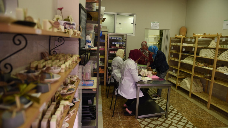 Najwa (rear) and her employees prepare orders at their shop in Zarqa, Jordan.