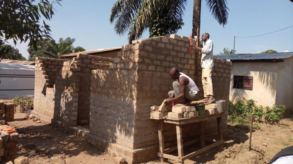 Two men build a house as part of a UNHCR construction project in the Malemaka district of Bangui, Central African Republic, November 2017.