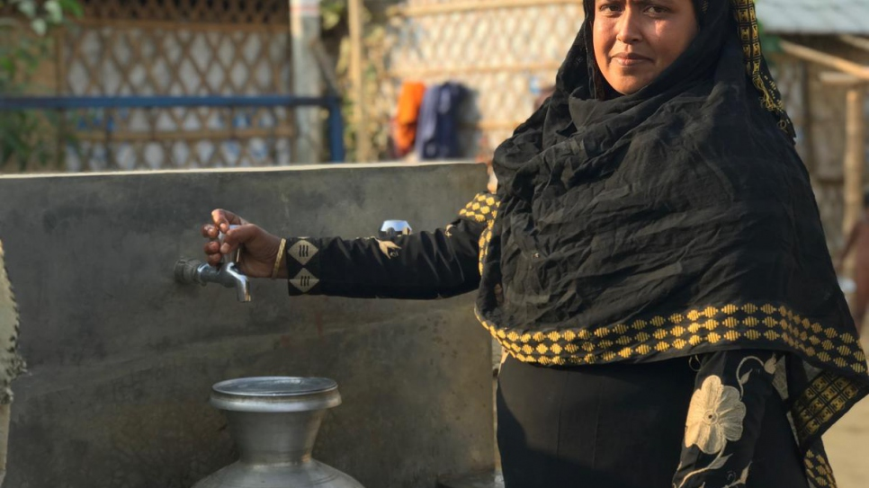 Rohingya mother Lalu Begum, 32, collects water at the solar-powered tap near her house in Kutupalong refugee settlement, Bangladesh.