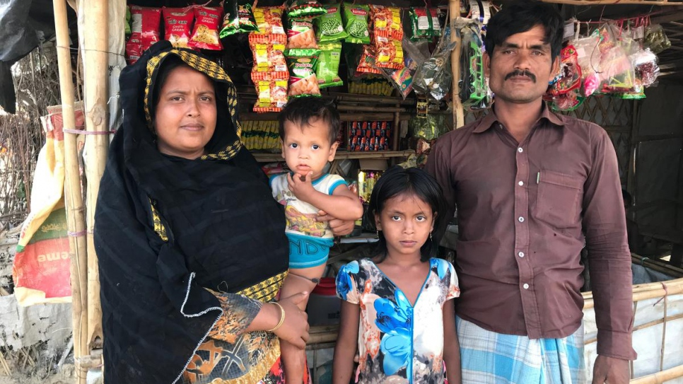 Rohingya parents Lalu Begum and Nurul Salam stand in front of their tea shop in Kutupalong refugee settlement, Bangladesh, with two of their children.