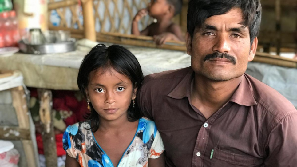 Nurul Salam, 35, sits with his eight-year-old daughter, Janatara, in the tea shop he runs in Kutupalong refugee settlement, Bangladesh.