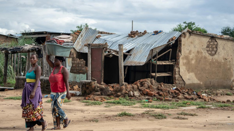 Two women walk past a house destroyed during Cyclone Idai's landfall at Tongogara refugee camp in Chipinge district, south-eastern Zimbabwe.