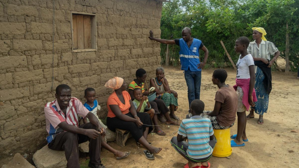 A UNHCR worker talks with the family of Magdalena Niragire at Tongogara refugee camp, Zimbabwe.