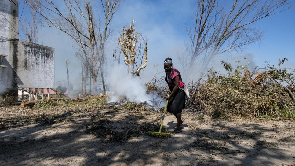 A woman sweeps the city streets of Dondo, Mozambique, cleaning and burning the branches and fallen leaves in the aftermath of Cyclone Idai.
