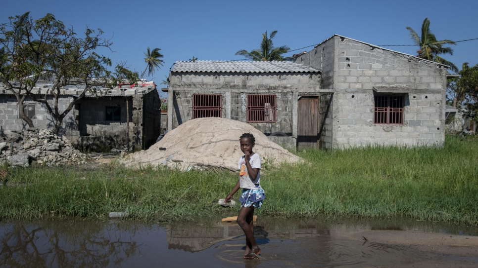 A young girl walks barefoot into the flood waters in the aftermath of Cyclone Idai in Beira, Mozambique.