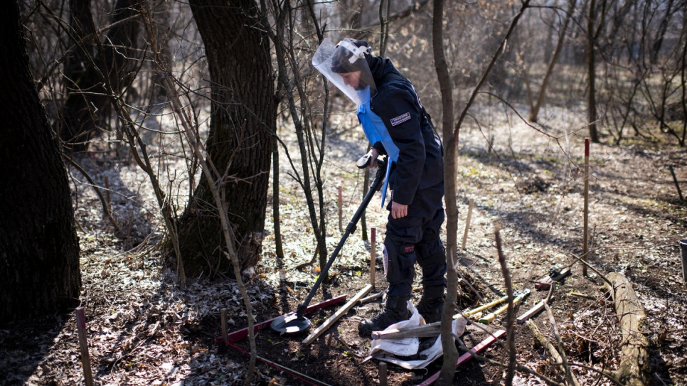 Tetiana uses a metal detector to search for landmines in a forest near Ozerne, Donbas.