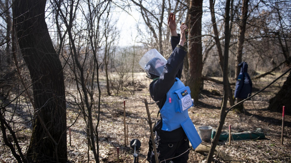 Tetiana clips tree branches in her search for landmines and tripwires.