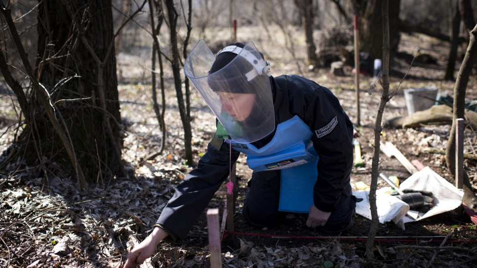 Deminer Tetiana Nikiforova, 37, searches through dried leaves for landmines.