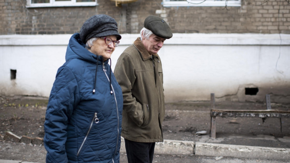 Valentyna and Volodymyr go for a walk outside their new home in the city of Toretsk.